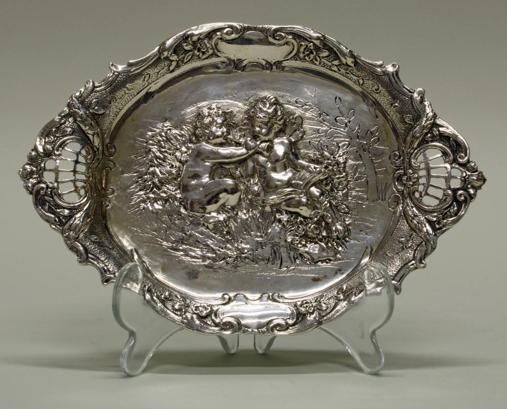 Kleine Amorettenplatte, Silber 800, deutsch, ovalförmig, musizierende Amoretten im Relief, zwei Handhaben mit durchbrochenem Gitterwerk, 19.5 x 13 cm, ca. 151 g