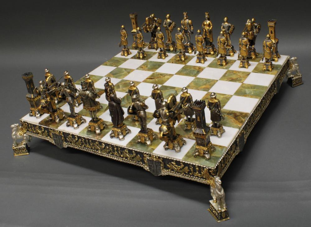 Schachspiel, 33-tlg., Italien, Ende 20. Jh., Piero Benzoni, Spielbrett mit Onyx und einer Einfassung aus Metallguss, 32 Schachfiguren im Ritterstil aus Metallguss, teils vergoldet, 8.5 x 51.5 x 51.5 cm, 8.5-11 cm hoch.