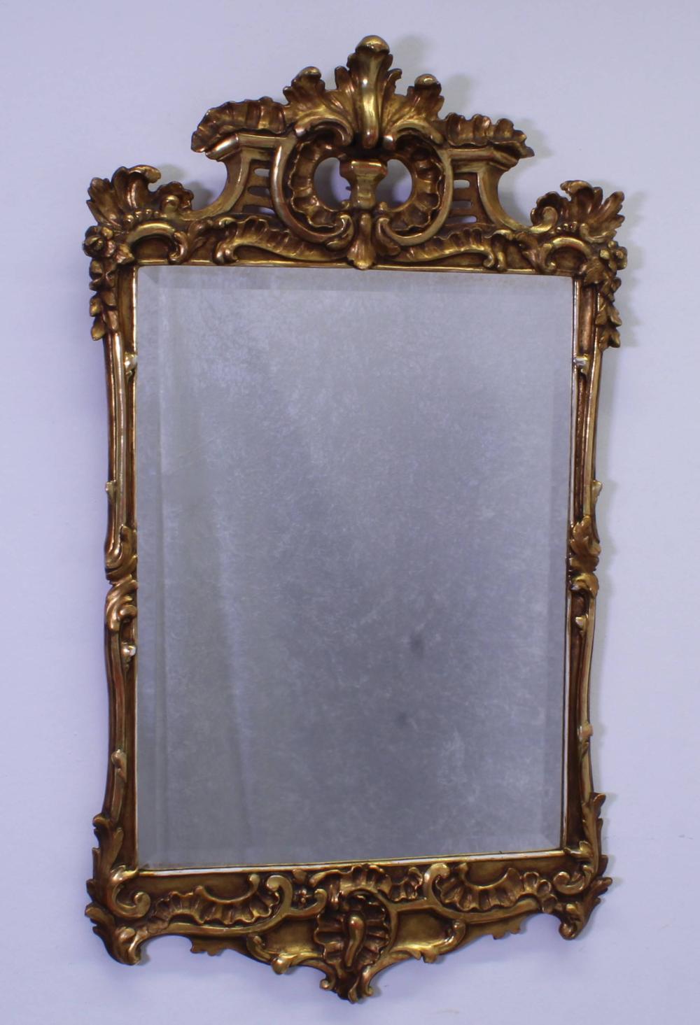 Wandspiegel, 18. Jh., Rahmen Holz geschnitzt, mehrfach durchbrochenes Dekor mit Voluten und Akanthusblättern, vergoldet, erneuertes facettiertes Spiegelglas, 110 x 63 cm, rest. Zustand