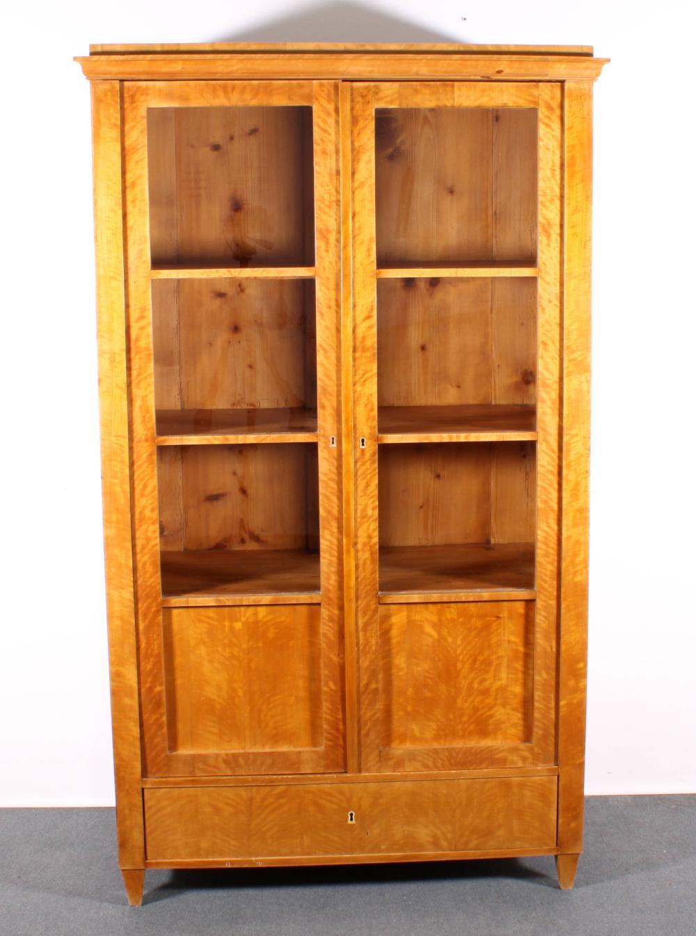Vitrine/Bücherschrank, Biedermeier, um 1825, Birke geflammt furniert auf Weichholz, zweitüriger Korpus auf konischen Füßen, Sockelschub, darüber zwei Türen mit je drei verglasten Fenstern, leicht vorkragende Giebelleiste, innen drei Einlegeböden, 17