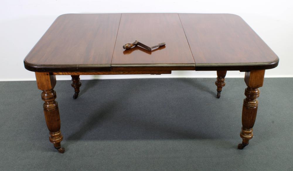 Esstisch, wohl viktorianisch, 19. Jh., Mahagoni, große an den Ecken gerundete Platte, raffinierte Ausziehmechanik per Kurbel mit Einlegeplatte, gedrechselte kannelierte Beine auf Rollen, ca. 80 x 100 (145) x 100 cm