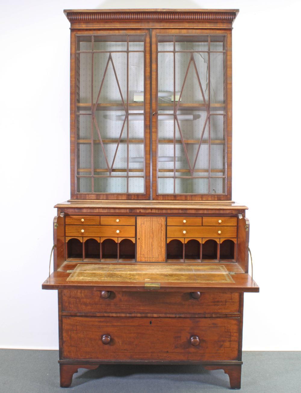 """Aufsatz-Schreibkommode / """"Secretaire Bookcase"""", England, frühes 19. Jh., Mahagoni, Unterteil mit drei Schüben, hiervon der oberste blind und als Schreibfach ausklappbar, innen Ledereinlage auf Schreibfläche, sechs kleine Schübe, acht offene Fächer u"""