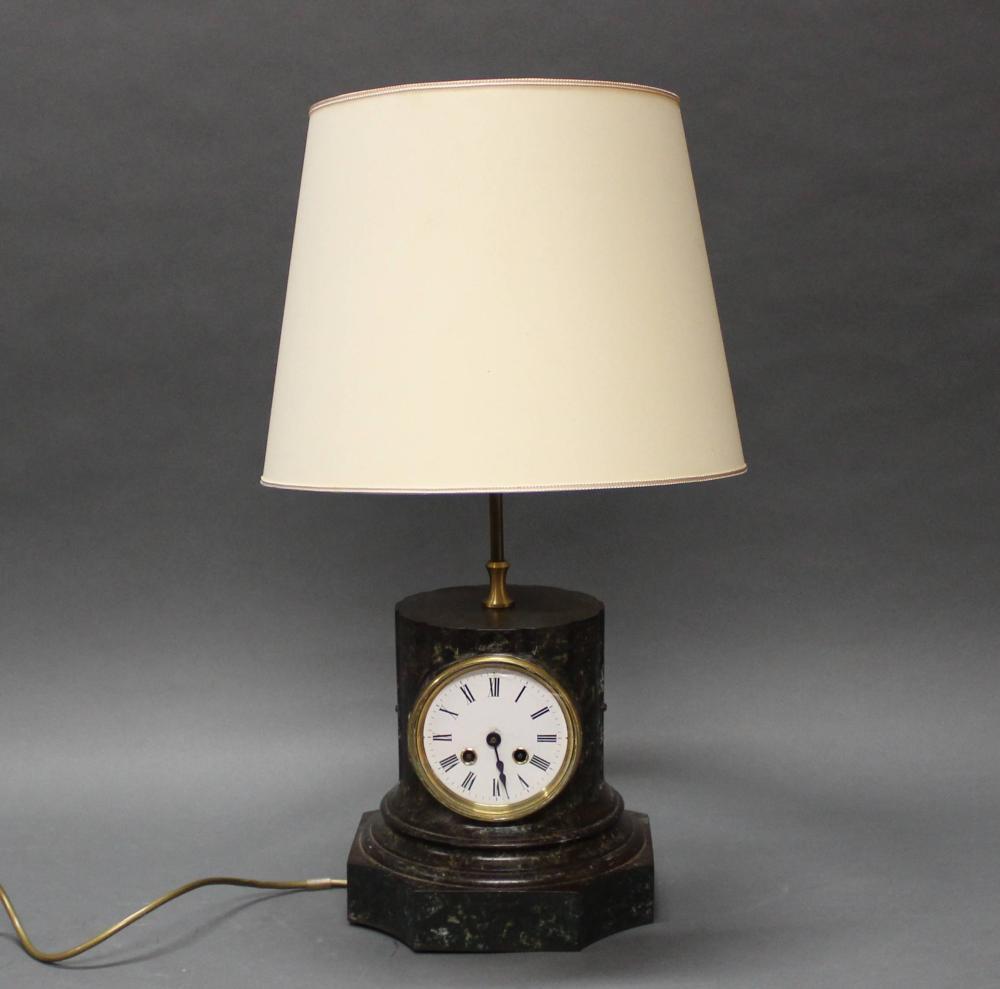 Lampenuhr, um 1900, bronzierter Metallsockel als Säulenstumpf, integrierte Uhr mit Aufzugswerk, weißes Emailzifferblatt, zweiflammig, elektrifiziert, heller Lichtschirm, 65 cm hoch, Altersspuren, Zifferblatt etwas bestoßen, Werk ungeprüft