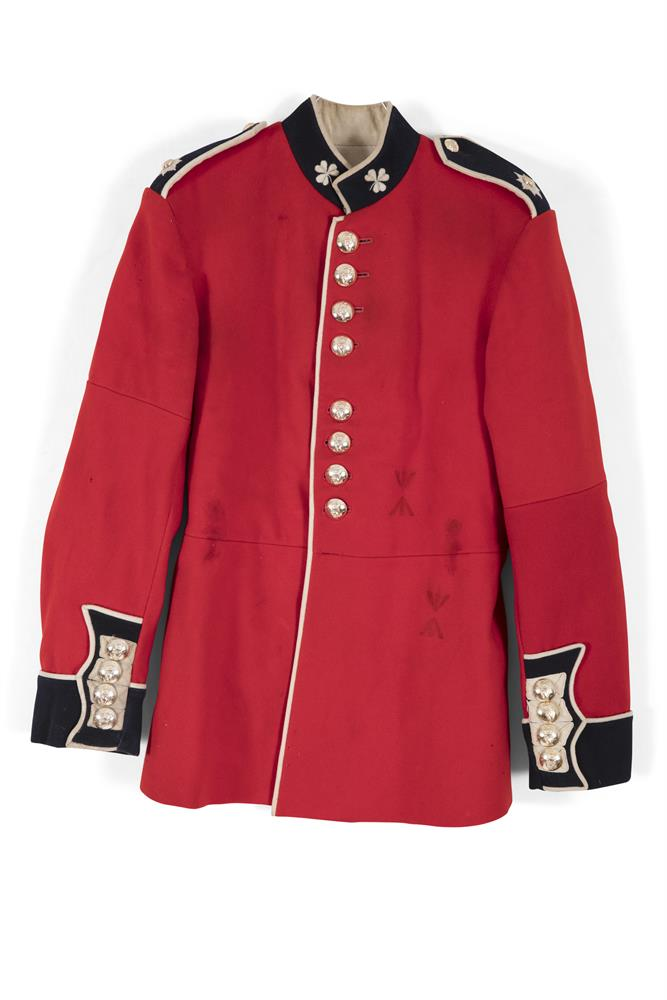 AN IRISH GUARDS CEREMONIAL TUNIC, 1959 pattern, in red and navy cloth, with shoulder straps and collar woven with twin shamrock motifs and applied with a double string of buttons embellished with a harp and crown, repeated to the cuffs.