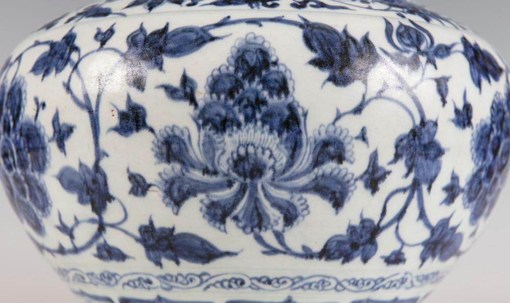 A RARE BLUE AND WHITE PEONY JAR, 'Guan' mid 14th century, the squat baluster shaped body painted in a strong tone of underglaze blue with a broad band of six alternating lotus and peony blooms, linked by vines and scrolling foliage, contained within