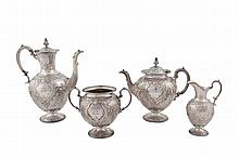 A VICTORIAN FOUR PIECE SILVER TEA AND COFFEE SERVICE, Sheffield 1864, maker's mark of Martin Hall & Co., comprising coffee pot, tea pot, sugar bowl and creamer, each of conforming design, chased and embossed with scrolling foliate decoration surround