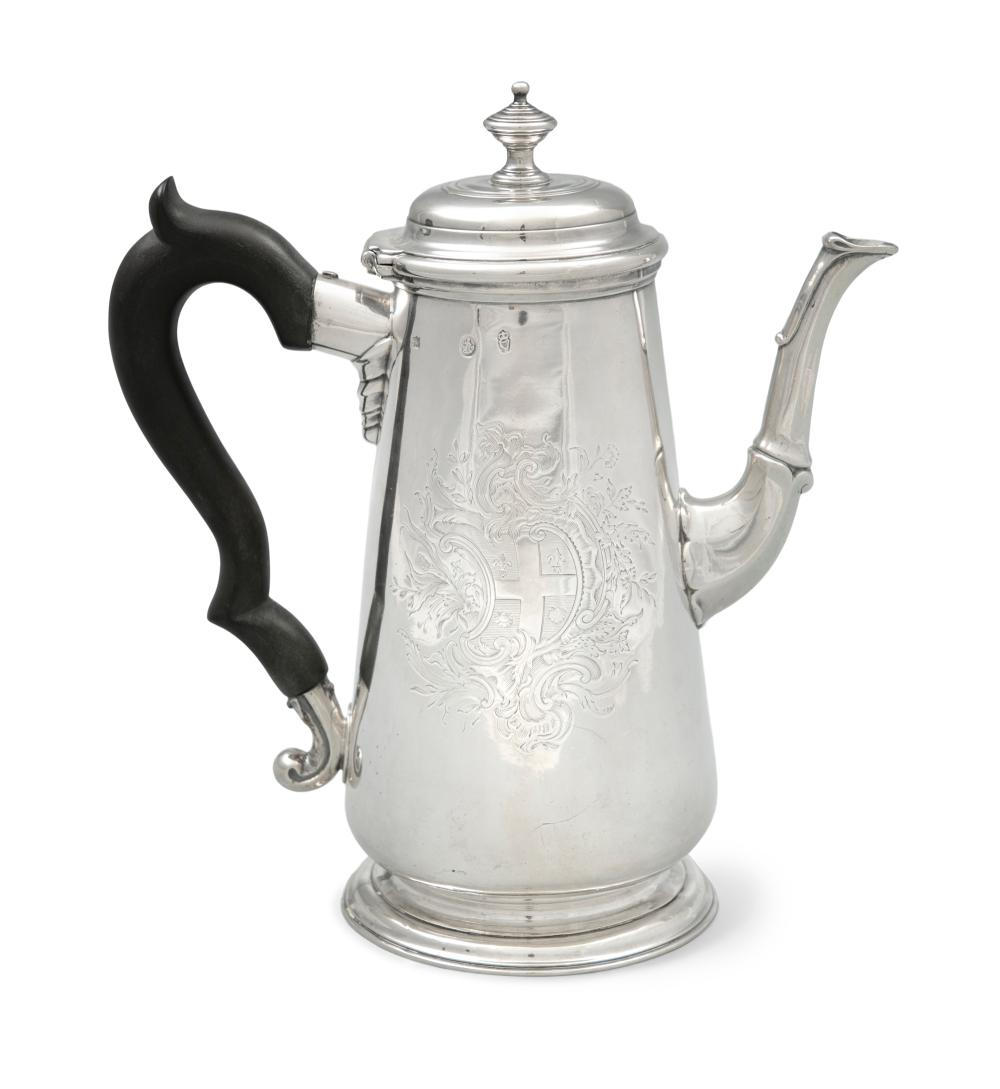 A FINE IRISH GEORGE II SILVER COFFEE POT, by John Hamilton, Dublin c.1745, of tapering form with hinged domed lid and finial, the plain body engraved with an armorial crest within leaf cartouche, on a circular spreading foot, with timber handle, (c.