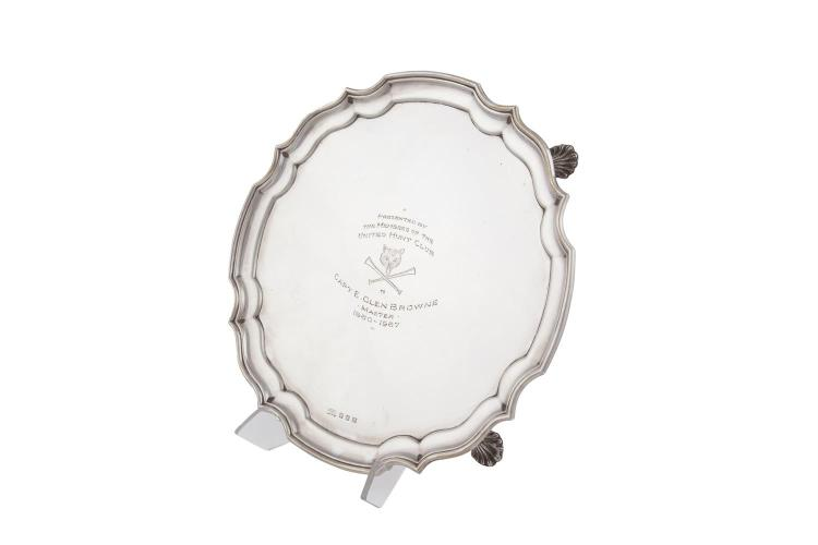 A GEORGIAN STYLE SILVER SALVER, Dublin 1964, mark of William Egan of Cork, of shaped circular form with pie crust rim, inscribed to Capt. E. Glen Browne by the United Hunt Club, (c.755g). 30cm diameter