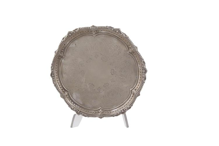 A VICTORIAN SILVER CARD TRAY, London 1889, mark of Martin & Hall, retailed by Goldsmiths & Silversmiths Co. London, with cast bellflower and scroll banding, engraved reserve and raised on claw and ball feet, (c.265g). 20cm diameter
