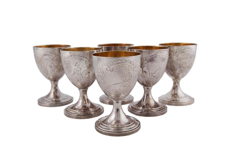 A SET OF SIX MODERN IRISH SILVER WINE GOBLETS, Dublin 1973, mark of Royal Irish Ltd., with gilt lined bowls, engraved with 'Dairy Maid' and other figural scenes, raised on spreading feet with reeded rims. 14.2cm high