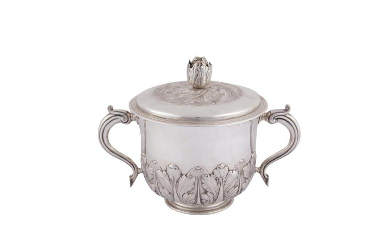 A VICTORIAN SILVER CIRCULAR PORRINGER, London 1886, mark of John Newton Martin, with twin handles, detachable lid with cast flower head, the lid and body decorated with repoussé chased and engraved foliage, and raised on rim foot, (c.746.5g). 19cm hi