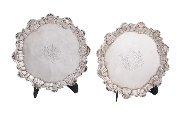 A NEAR PAIR OF GEORGE II SHAPED CIRCULAR SILVER CARD TRAYS, London 1754, mark of Dorothy Sarbitt, with raised shell and swag border, each engraved with individual crest and raised on three hoof capped feet (c.560g). Each 19cm diameter. (2)