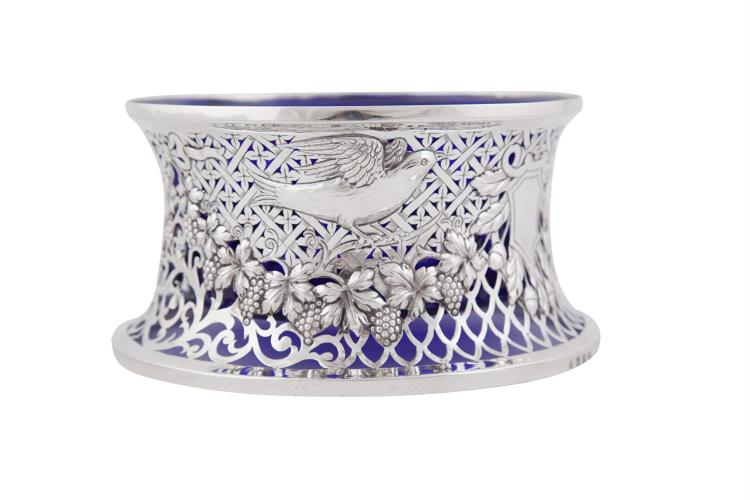 AN IRISH SILVER DISH RING, Dublin 1914, mark of S.D. Neill, Belfast, with pierced repousse, chased and engraved bird and vine decoration, with blue glass liner. 19cm diameter