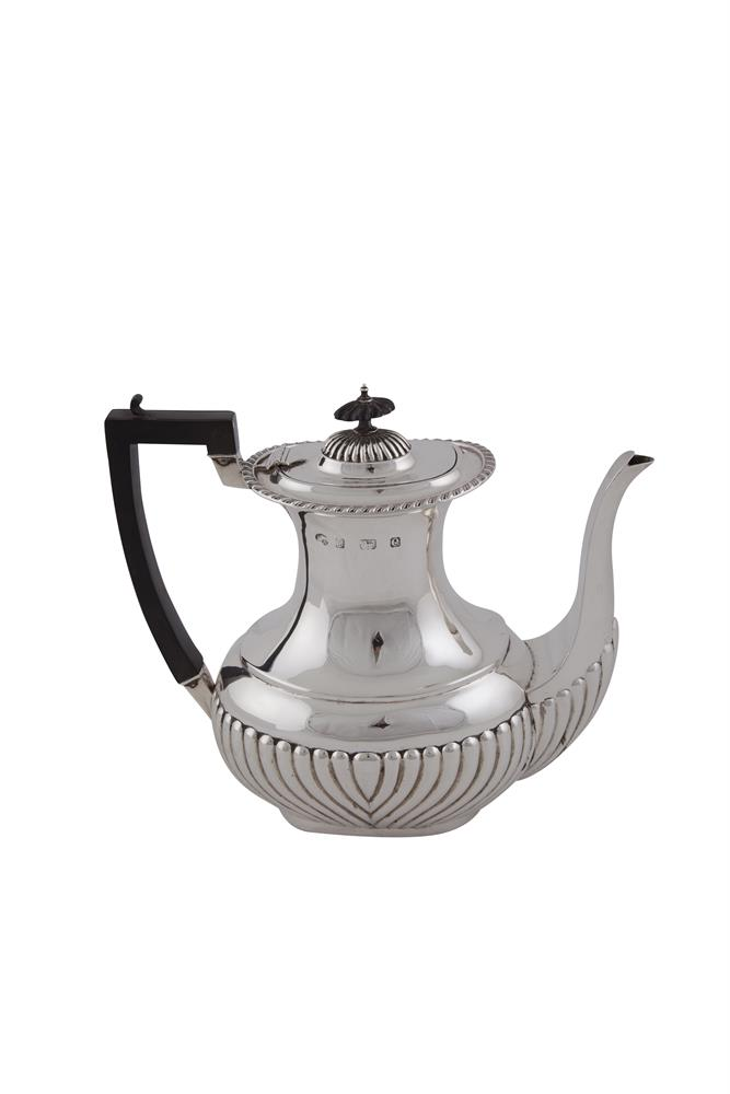 AN EDWARDIAN PLAIN SILVER OVAL COFFEE POT, Birmingham 1904, the lower baluster body with fluted decoration and ebonised angular handle, (c. 700g including handle). 25cm wide over handle and spout