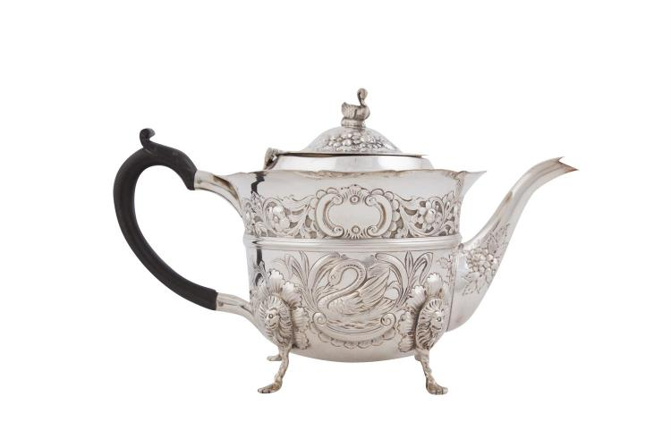 AN IRISH EDWARDIAN SILVER TEA POT, Dublin 1902, mark of Charles Lamb, in the Georgian Revival taste, the hinged cover with cast swan finial, applied with 'c' scroll ebon handle, the body chased and embossed with swan and fox motifs contained within s