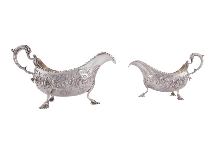 A PAIR OF IRISH MID-GEORGIAN SILVER SAUCE BOATS, Dublin c.1760, mark of William Townsend, of large proportions, the oval form with scroll handles, gadroon rims and with repoussé chased and engraved later decoration, raised on shell feet, (c.1057.5g).
