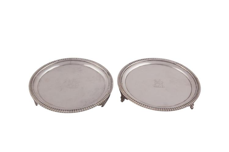 A PAIR OF GEORGE III SILVER CARD TRAYS, London 1806, mark of Naphthäli Hart, of circular form with beaded rim and raised on reeded bracket feet, (c.528.5g). 14.5cm diameter