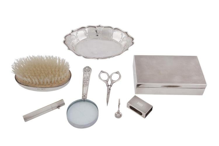 A MISCELLANEOUS COLLECTION OF SILVER DRESSING TABLE ITEMS, comprising:- a silver mounted cigarette box; a match box cover; a silver mounted clothes brush; a silver dish; a magnifying glass; sewing scissors; a small cylindrical etui; a money clip