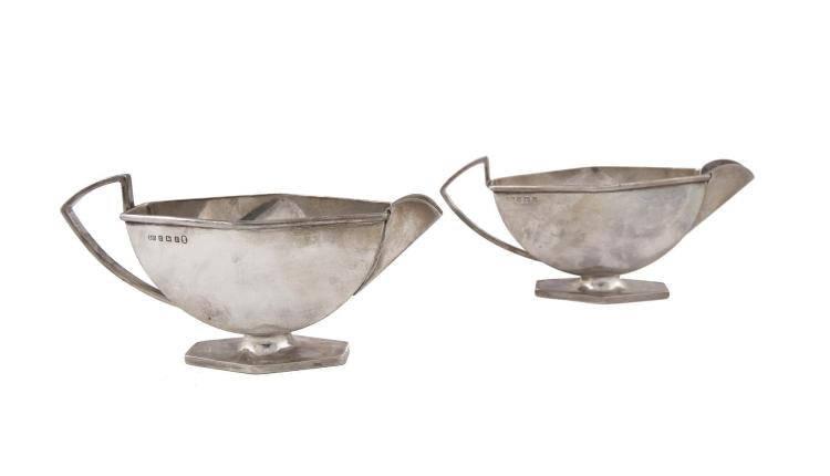 A PAIR OF ART DECO SILVER SAUCE BOATS, Birmingham 1934, 1935, mark of Adolph Scott, one with Silver Jubilee mark, of elongated angled form, (c.311g). 18cm wide over handle and spout
