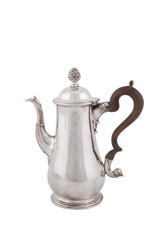 AN IRISH GEORGE III PEAR SHAPED COFFEE POT, Dublin 1775, mark of William Ward, applied with acorn finial and walnut 's' scroll handle, the plain body raise on circular spreading base, (c.995g all in including handle). 26.5cm high