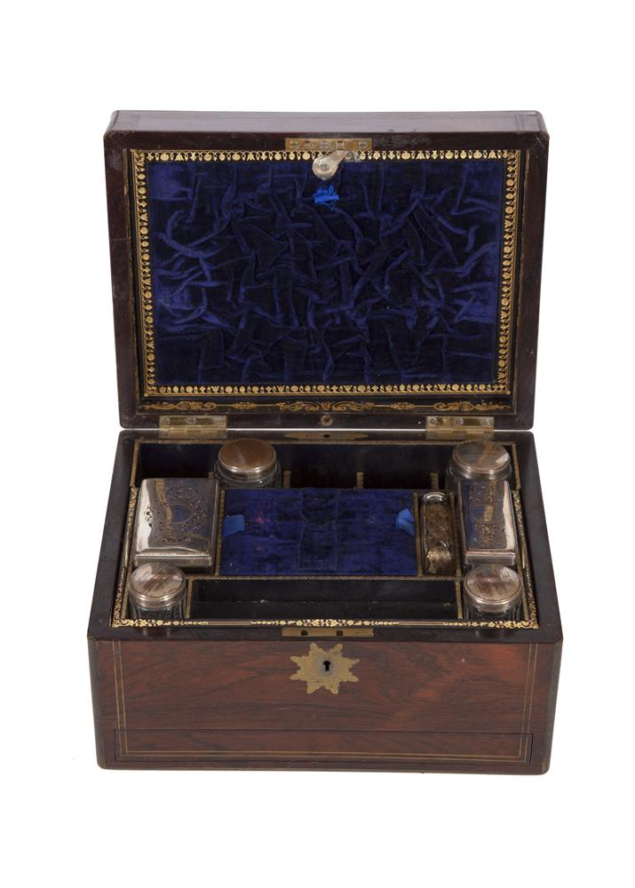A 19TH CENTURY ROSEWOOD AND BRASS INLAID TRAVELLING BOX, by Austin of Dublin, the rectangular case enclosing a velvet lined and compartmented interior fitted with glass bottles and accessories, over a single concealed drawer. 31 x 23cm