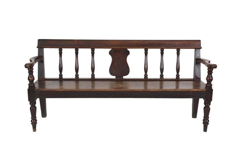 A 19TH CENTURY OAK FRAMED HALL SETTLE, the rectangular back centred with a vacant shield shaped reserve flanked by turned baluster supports, solid panel seat and baluster legs. 189cm wide