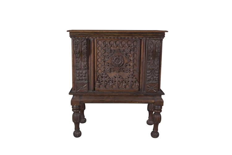 A GOTHIC OAK CABINET ON STAND, partially 17th century, fitted with rectangular top above heavy blind fret carved cupboard, centred with a foliate boss and flanked with acanthus carved corbels, the base on turned fluted supports. 131cm high x 110cm wi