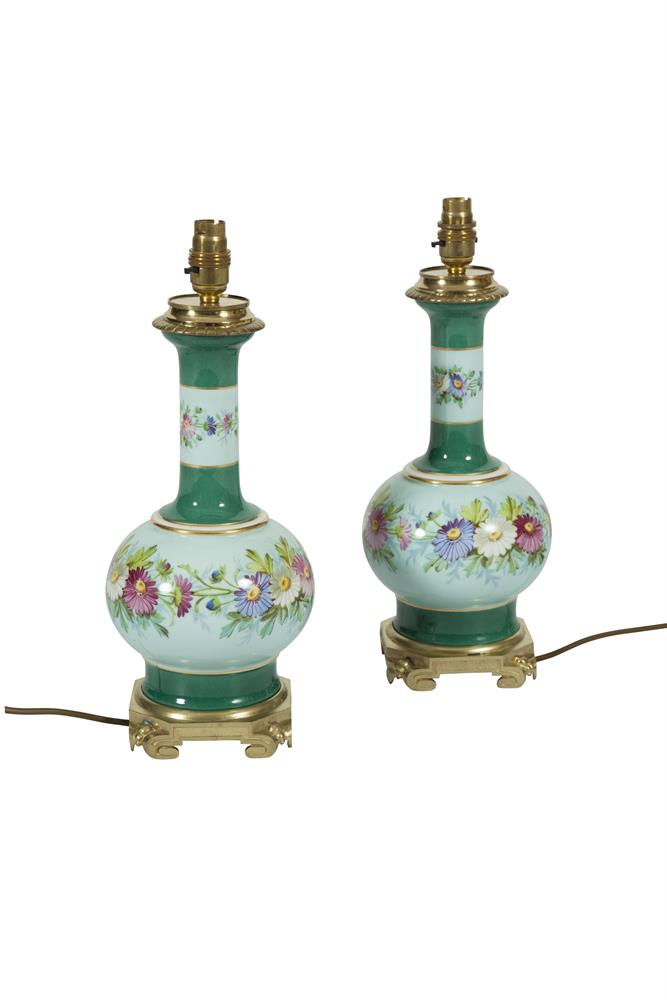 A PAIR OF LATE 19TH CENTURY PORCELAIN AND ORMOLU MOUNTED TABLE LAMPS, of circular baluster form with foliate decoration and green and gilt banding, complete with silk shades, adapted for electricity. 35cm high without the shades