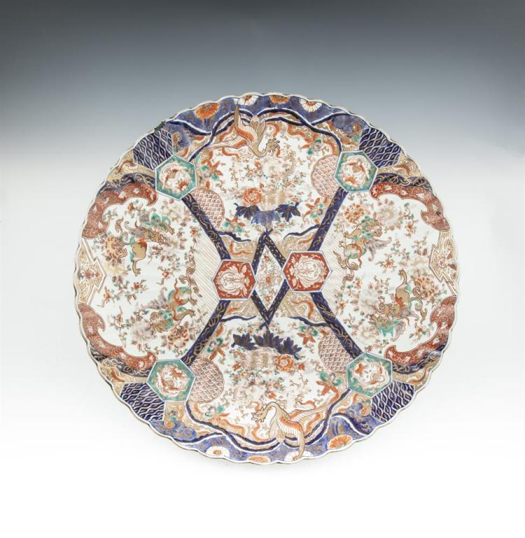 A LARGE JAPANESE IMARI PORCELAIN CHARGER, Meiji period, of shallow circular form, decorated with panels of foliage in traditional palette. 56cm diameter
