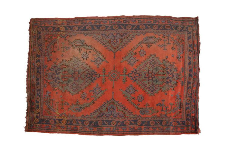AN AFGHAN WOOL RUG, the red ground bearing two large opposing medallions in green hues, surrounded by symmetrical geometric motifs with sky blue highlights, to a band of foliate rosettes against a navy ground and contained within a further row of gra