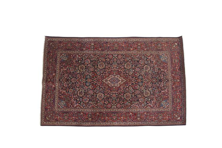 A FINE PERSIAN WOOL RUG, the large rectangular field woven with central medallion, filled with dense foliate design, within a broad similarly decorated border and guard stripes, against a deep crimson ground. 134 x 204cm