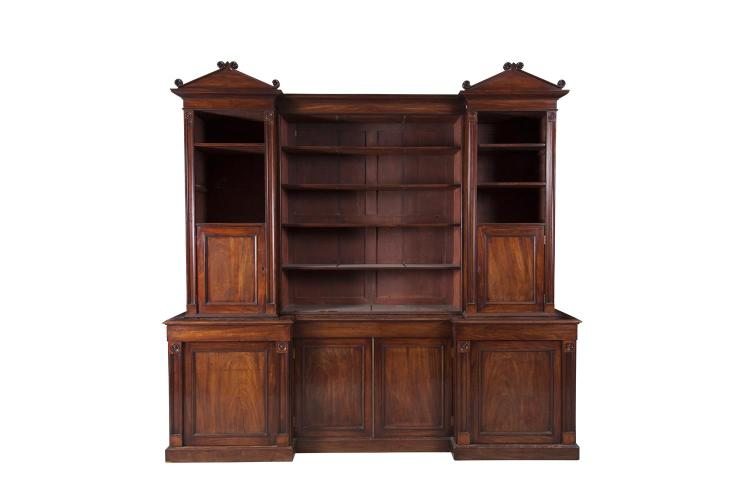 A WILLIAM IV MAHOGANY BREAKFRONT BOOKCASE, with triangle pediment and carved roundels. 260cm wide, 260cm high, 53cm deep