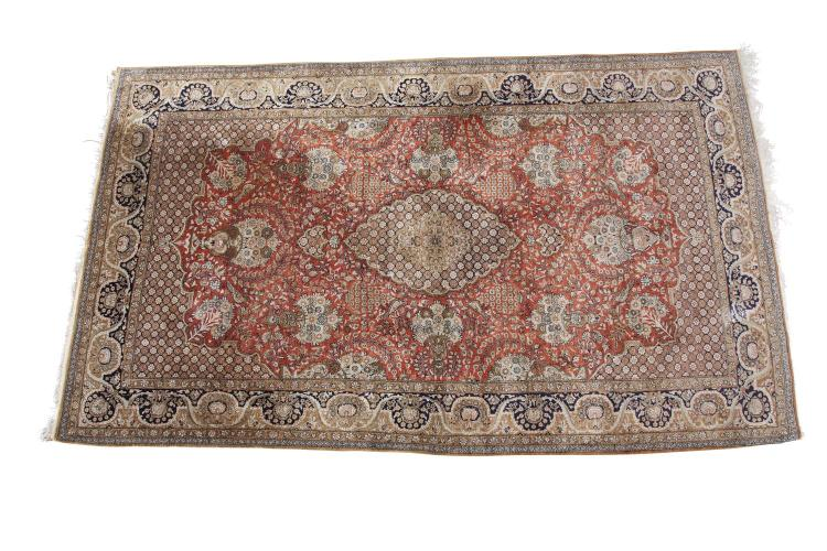***PLEASE NOTE ESTIMATE SHOULD READ €500-800 IN THE PRINTED CATALOGUE*** A PERSIAN SILK AND WOOL RUG, 20th century, the large rectangular field centred with a honeycomb medallion against a red ground, surrounded by birds and floral groups, and conta