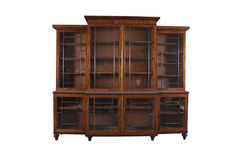 A GEORGE IV MAHOGANY FOUR DOOR BREAKFRONT BOOKCASE, the upper section fitted with moulded cornice above geometric glazed panel doors enclosing adjustable shelving, the lower section with corresponding glazed doors and supported on turned and reeded f