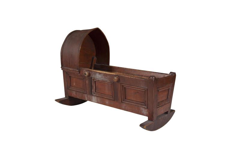 A VICTORIAN STAMPED PINE CHILD'S CRADLE, mid 19th century, with arched hood and tapering panelled sides, the interior with seven fixed support bars, on curved rocker feet. 88cm wide