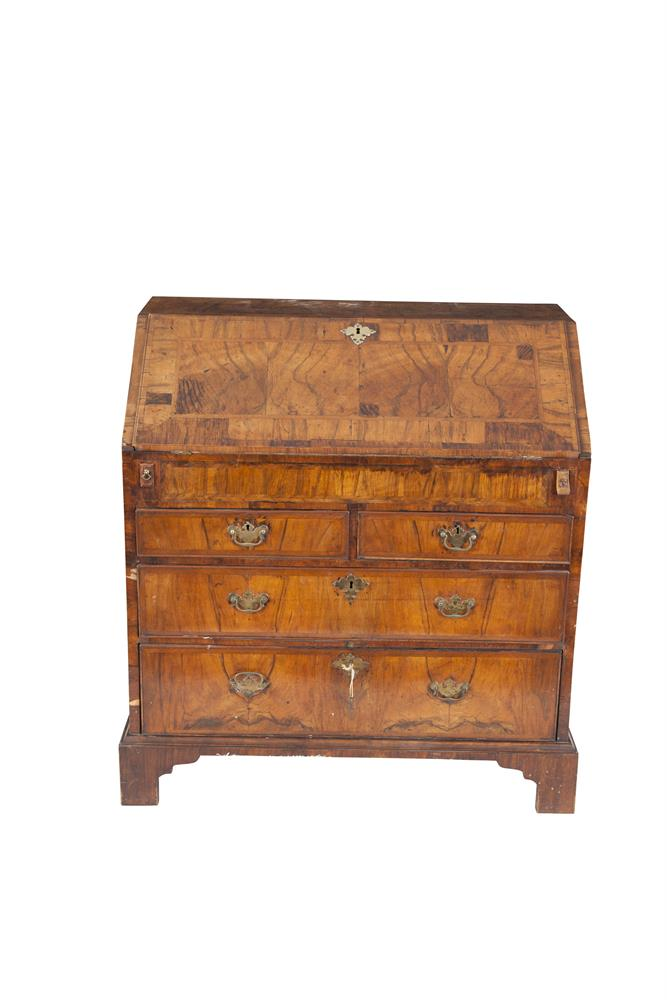 AN EARLY GEORGIAN WALNUT SLOPE-FRONT BUREAU, c.1720, with feathered inlay top and cross-banded slope opening to reveal an arrangement of cupboards and compartments, with two short and two long chest drawers on outset bracket feet. 96cm wide