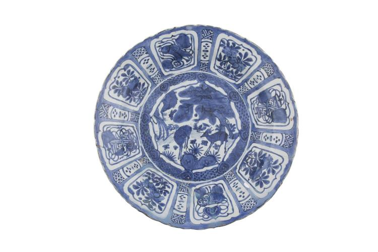A CHINESE MING DYNASTY BLUE AND WHITE 'KRAAK' PORCELAIN CHARGER, Wanzi (1573-1619), of deep circular form, the central reserve painted with deer in a rocky landscape encircled by segmented radial panels filled with various auspicious objects. 49cm di