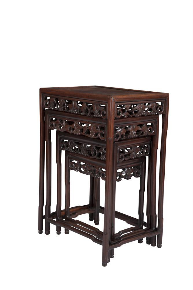 A NEST OF FOUR CHINESE CHERRYWOOD TABLES, of graduated size, each with dished rectangular top and foliate carved frieze. The largest 50 x 36 x 71cm high