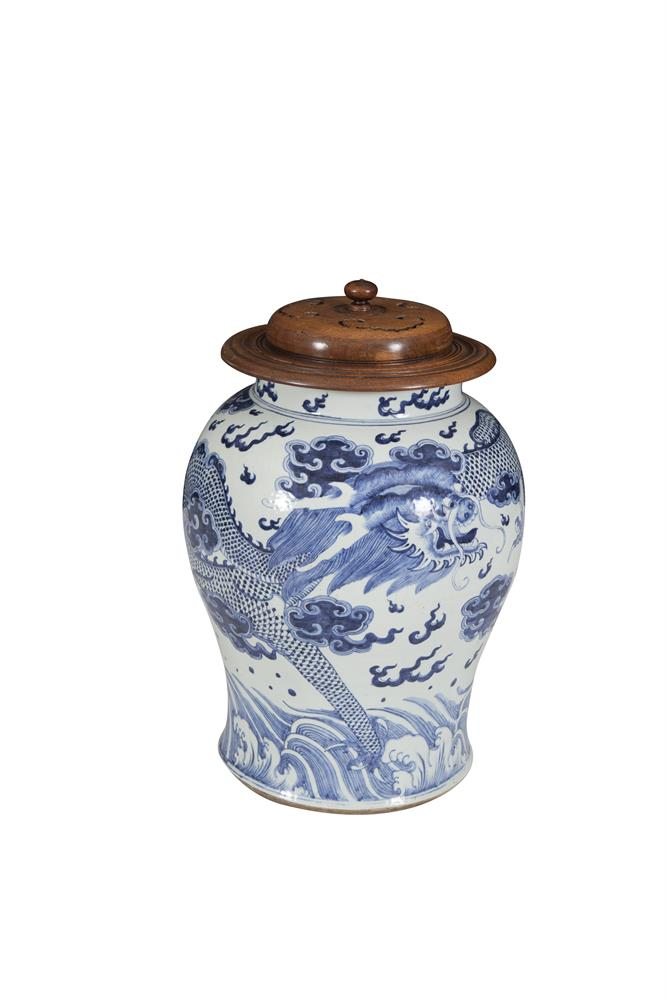 A LARGE CHINESE PORCELAIN BLUE AND WHITE STORAGE JAR AND COVER, in the Ming style, the baluster shaped body decorated with dragons in flight above a band of rolling waves. 49cm tallProvenance: Purchased in London in the 1950s by the current vendor.
