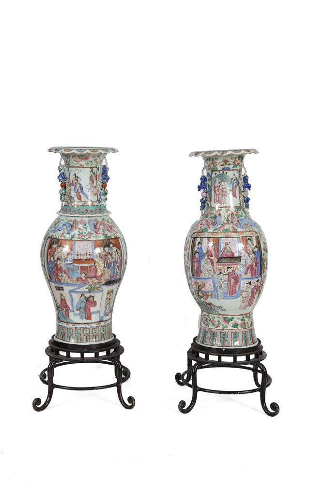 TWO SIMILAR CANTONESE PORCELAIN BALUSTER FLOOR JARS, with figural decoration in panels. 60cm high; together with a pair of metal stands
