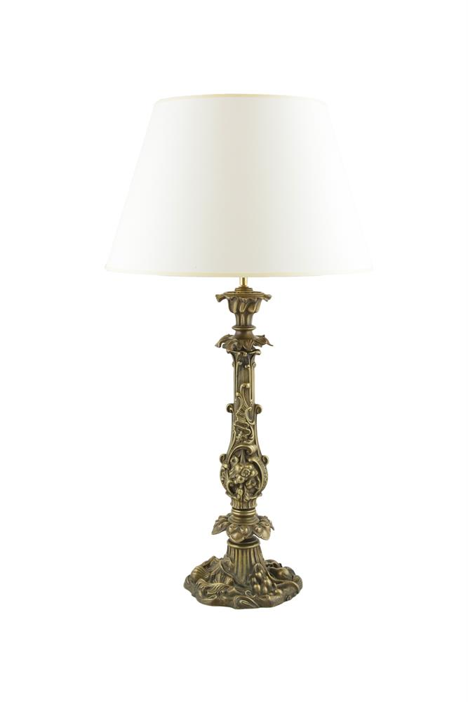 A CAST BRASS TABLE LAMP, the organic form column cast with foliate motifs, and raised on a shaped circular naturalistic spreading base, adapted for electricity, with a paper shade. 47cm high