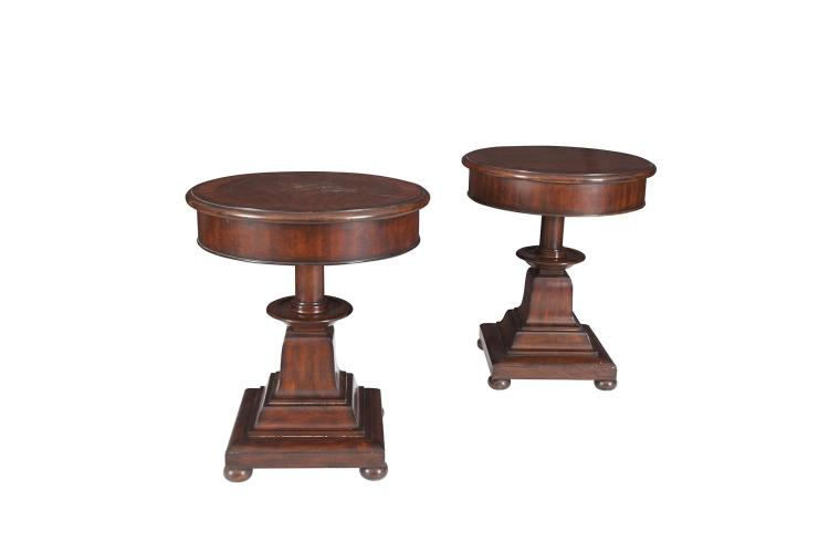A PAIR 'ANGLESEY' OCCASIONAL TABLES BY RALPH LAUREN, the crossbanded mahogany tops, above a deep frieze and supported on a squared and turned centre column, on stepped plinth base and bun feet. Each 57cm diameter, 68cm high