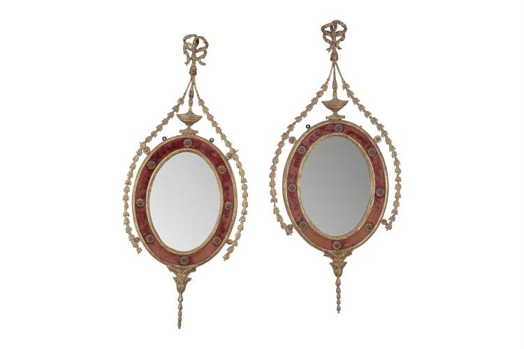 A PAIR OF GILTWOOD NEO-CLASSICAL STYLE OVAL WALL MIRRORS, 19th century, each fitted with oval bevel glass plate within a velvet and rosette border surmounted by an urn and ribbon tied crest with trailing bellflowers to each side. 100cm high x 43.5cm