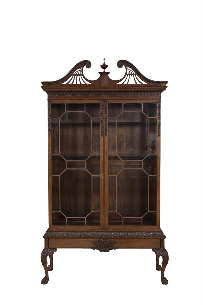 A GEORGIAN STYLE MAHOGANY TWO DOOR DISPLAY CABINET, of rectangular form, surmounted by broken swan neck cornice, centred with pointed finial over twin astragal glazed panel doors, enclosing shelved interior, on leaf carved base, with acanthus capped