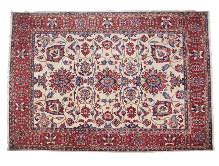 A LARGE ZIEGLER PATTERN WOOL CARPET, the large rectangular field woven with intertwined tendrils and flower heads on a cream ground, within a crimson broad and narrow border, decorated with geometric pattern and guard striped. 272 x 373cm