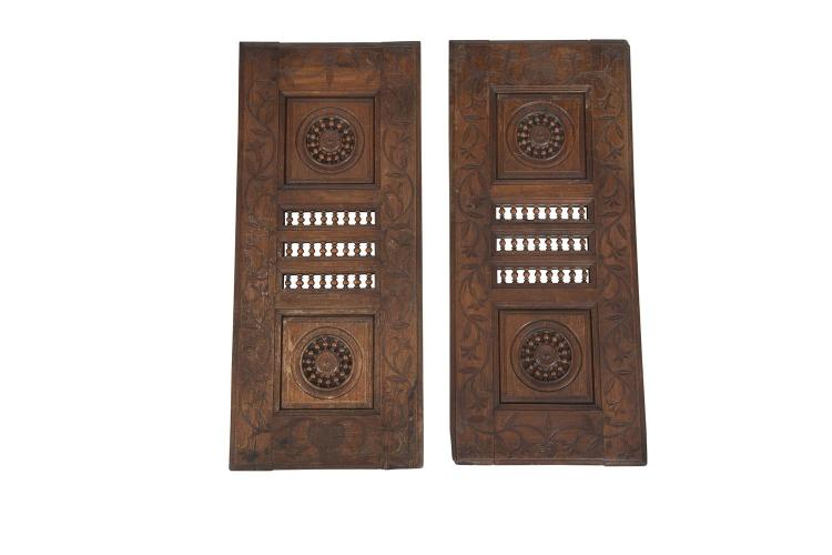 A PAIR OF 19TH CENTURY FRENCH PROVINCIAL CARVED FRUITWOOD CABINET DOORS, each set with twin roundel panels and three rows of turned balusters, surrounded by a border of interlinked foliage. 100 x 42cm