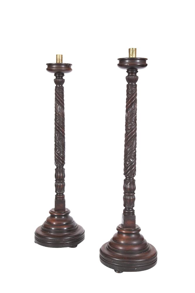 A PAIR OF COMPOSED MAHOGANY PILLAR TORCHERES, the circular sconces raised on spiral leaf carved columns, and raised on stepped circular bases. 154cm high
