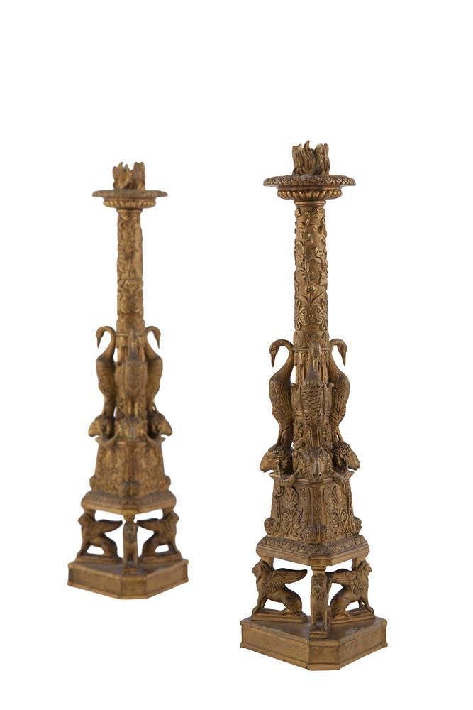 A PAIR OF EMPIRE GILDED METAL TRIANGULAR COLUMN CANDLESTICKS, decorated with rams' heads and exotic birds, raised on three sphinxes on platform base