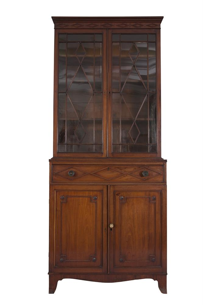 ***PLEASE NOTE THIS LOT IS INCORRECTLY NUMBERED IN THE PRINTED CATALOGUE*** A GEORGE IV MAHOGANY BOOKCASE, of upright rectangular form, fitted with a stepped cornice and overlaid with a row of seven lozenges, over twin glazed panel doors enclosing a