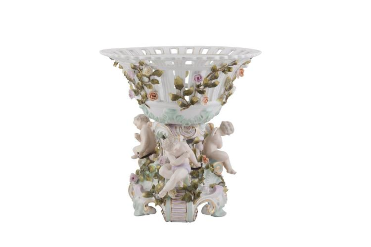 A MEISSEN POLYCHROME PORCELAIN TABLE CENTREPIECE, in the form of a basket supported on a column flanked by three winged cherubs on scrolled feet. 32cm high